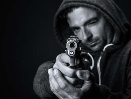 Young white man aiming a gun, selective focus on the barrel.