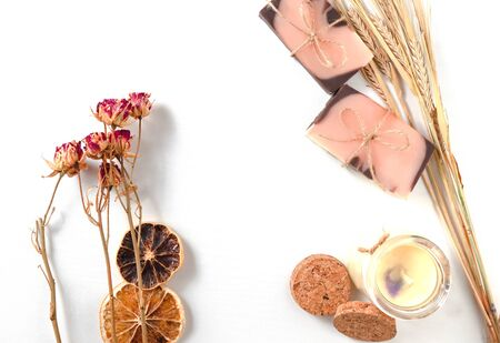 Flat lay composition with two handmade soaps of brown-pink color with an orange tint, dried slices of oranges, roses flowers, pastel vanila candle and spikes of wheat on a white background with wooden texture. Horizontal photo. Handmade cosmetics concept with natural ingredients for personal care, bath, shower and spa. Citrus oranges products.