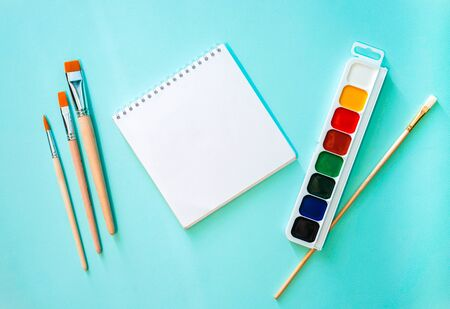 Watercolor paint with white, yellow, red, green, blue and black colors, three light beige brushes with orange pile, one brush with white pile and wooden texture and white clear sheet of note book on a light blue background. Horizontal photo. Flat lay minimalistic composition. Back to school, college, education concept. Space for text, copy space. Stationery. Art supplies idea. The note book in the centr, in the left are three brushes and the watercolor paints with one brush in the right part of the picture.