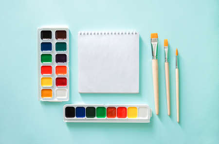 Two sets of color Watercolor paints, three light beige brushes with orange pile and wooden texture and white clear sheet of note book on a light blue background.