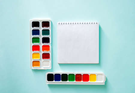 Two sets of color Watercolor paints and white clear sheet of note book on a light blue background. Horizontal photo. Flat lay minimalistic composition. Stock Photo