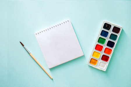 Watercolor paint , light beige brushes with brown pile and wooden texture and white clear sheet of note book on a light blue background.