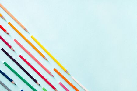 Multicolored pencils located diagonally in the lower left corner of the photo. Horizontal photo. Flat lay minimalistic composition on a light blue background. Office supplies concept. Back to school, college, education concept. Space for text, copy space. Stationery.