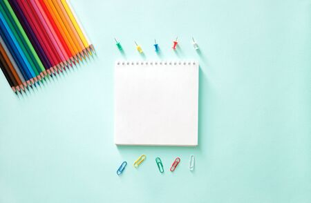 Color pencils, paper clips, stationery buttons on a light blue background. Horizontal photo. Flat lay minimalistic composition. Back to school, college, education concept. Space for text, copy space. Stationery. Art supplies idea.