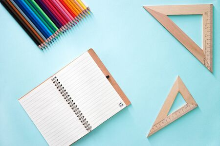 Color pencils, two wooden rulers triangles and clear sheet note book on a light blue background. Horizontal photo. Flat lay minimalistic composition. Back to school, college, education concept. Space for text, copy space. Stationery. Art supplies idea.