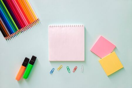 Color pencils, stationery stickers pink and lemon color, paper clips, orange and green highlighter and white clear sheet of note book on a light blue background. Horizontal photo. Flat lay minimalistic composition. Back to school, college, education concept. Space for text, copy space. Stationery. Art supplies idea.