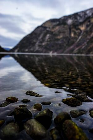 Bottom view of the breathtaking northern landscape. Fjord in norway. Vertical photo. Fjord on the background of water.