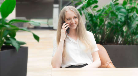 Portrait of a cheerful young caucasian blond business woman sitting on the table, talking at phone and smiling. Concept of successful young women in a corporation. Concept of successful young women in a corporation. Girl in a white shirt. Horizontal photo. Blurred background. Plants on the background.