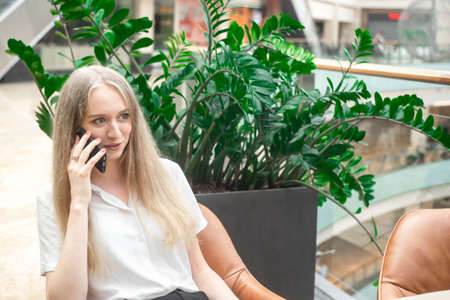 Portrait of a cheerful young caucasian blond business woman sitting on the table, talking at phone and smiling. Surprised face. Concept of successful young women in a corporation. . Girl in a white shirt. Horizontal photo. Blurred background. Plants on the background.