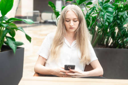 Portrait of a cheerful young caucasian blond business woman sitting on the table, holding and looking at phone and thinking. Concept of successful young women in a corporation. Girl in a white shirt. Horizontal photo. Blurred background. Plants on the background.