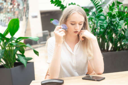 Portrait of a cheerful young caucasian blond business woman sitting on the table, holding and looking at phone and thinking. The girl holds glasses in her hand. On the table cover from glasses. Concept of successful young women in a corporation. Girl in a white shirt. Horizontal photo. Blurred background. Plants on the background. Stock Photo