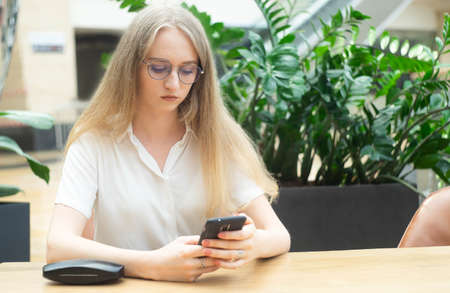 Portrait of a cheerful young caucasian blond business woman sitting on the table, holding and looking at phone and thinking. On the table cover from glasses. Concept of successful young women in a corporation. Girl in a white shirt. Horizontal photo. Blurred background. Plants on the background.