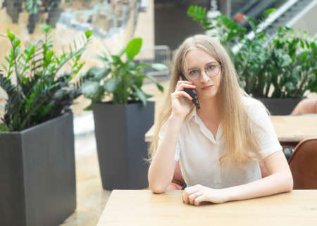 Portrait of a cheerful young caucasian blond business woman sitting on the table, talking at phone and looking at camera. Concept of successful young women in a corporation. Girl in a white shirt. Horizontal photo. Blurred background. Plants on the background.
