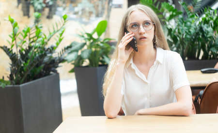 Portrait of a cheerful young caucasian blond business woman sitting on the table, talking at phone and looking away. Concept of successful young women in a corporation. Girl in a white shirt. Horizontal photo. Blurred background. Plants on the background. Stock Photo