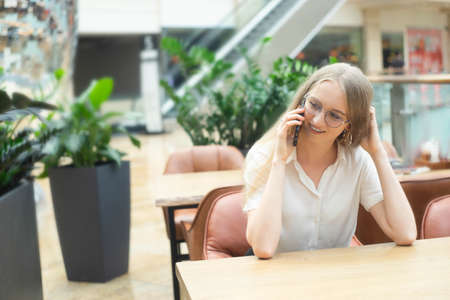 Portrait of a cheerful young caucasian blond business woman sitting on the table, talking at phone, smiling and looking away. Concept of successful young women in a corporation. Girl in a white shirt. Horizontal photo. Blurred background. Plants on the background.