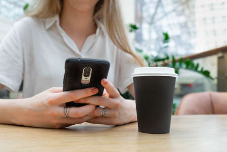 Cropped photo of cheerful young caucasian blond business woman in a white shirt typing on smartphone while resting on coffe break. Lifestyle concept. Concept of successful young women on coffe break. Nearby is a black cup of coffee.
