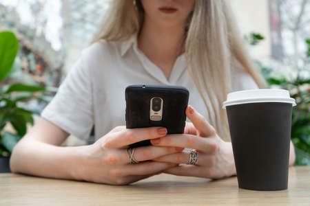 Cropped photo of cheerful young caucasian blond business woman in a white shirt smiling and typing on smartphone while resting on coffe break. Lifestyle concept. Concept of successful young women on coffe break. Nearby is a black cup of coffee.