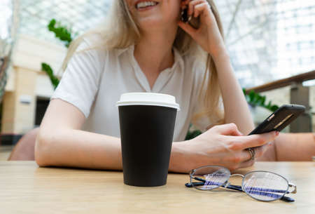 Close up photo of cheerful young caucasian blond business woman in a white shirt typing on smartphone while resting on coffe break. Lifestyle concept. Concept of successful young women on coffe break. Nearby is a plastic cup of coffee. Stock Photo