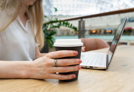Close up photo of notebook being used by young caucasian business woman in a striped jacket sitting at the table. Nearby is a plastic cup of coffee. Business woman Concept. Lifestyle concept.