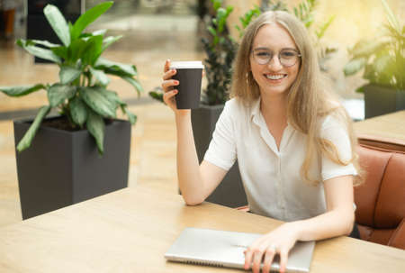 Portrait of a cheerful young caucasian blond business woman sitting on the table, holding notebook, smiling and looking at camera. Concept of successful young women in a corporation. Girl in a white shirt. Horizontal photo. Blurred background. Plants on the background.