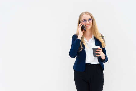 Portrait of a young European blonde business woman is standing in front of a white wall, smiling, talking at the phone and holding coffee in her hand. She is dressed in black pants, blue jacket and a white short-sleeved shirt. Concept of successful young women. Lifestyle concept. Copy space. Space for text. Horizontal photo.