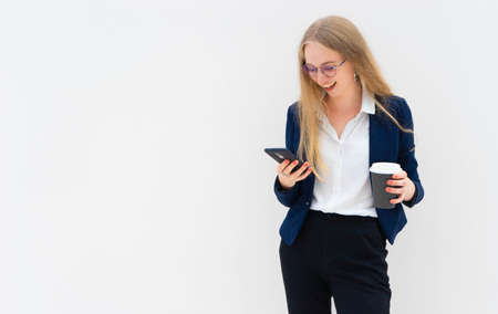 Portrait of a young European blonde business woman is standing in front of a white wall, smiling, looking at the phone and holding coffee in her hand. She is dressed in black pants, blue jacket and a white short-sleeved shirt. Concept of successful young women. Lifestyle concept. Copy space. Space for text. Horizontal photo.