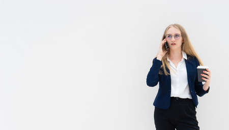 Portrait of a young European blonde business woman is standing in front of a white wall, smiling, talking to the phone and holding coffee in her hand. She is dressed in black pants, blue jacket and a white short-sleeved shirt. Surprised facial expression. Concept of successful young women. Lifestyle concept. Copy space. Space for text. Horizontal photo.