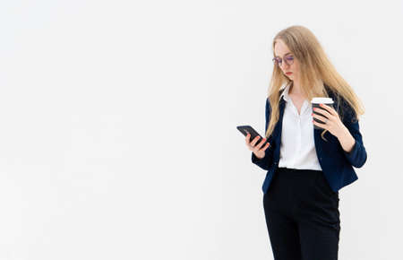 Portrait of a young European blonde business woman is standing in front of a white wall, looking at the phone and holding coffee in her hand. She is dressed in black pants, blue jacket and a white short-sleeved shirt. Concept of successful young women. Lifestyle concept. Copy space. Space for text. Horizontal photo.