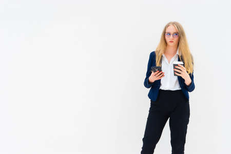 Portrait of a young European blonde business woman is standing in front of a white wall, looking away, and holding coffee and phone in her hands. She is dressed in black pants, blue jacket and a white short-sleeved shirt. Surprised facial expression. Concept of successful young women. Lifestyle concept. Horizontal photo. Copy space. Space for text.