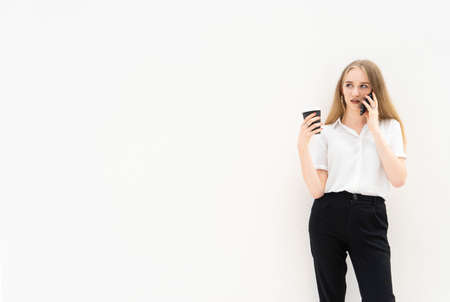 A portrait of young caucasian blonde business woman is standing in front of a white wall, talking to the phone, looking away, thinking and holding coffee in her hand. She is dressed in black pants and a white short-sleeved shirt. Concept of successful young women. Lifestyle concept. Copy space. Space for text. Stock Photo