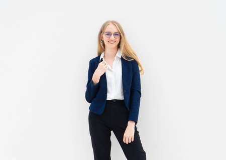 A portrait of young caucasian blonde business woman in glasses standing in front of a white wall, smiling and looking away. The right hand holds a jacket. She is dressed in black pants, blue jacket and a white short-sleeved shirt. Concept of successful young women. Lifestyle concept. Copy space. Space for text. Stock Photo