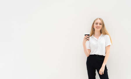 A portrait of caucasian blonde business woman is standing in front of a white wall, smiling, looking to the camera and holding coffee in her hand. She is dressed in black pants and a white short-sleeved shirt. Concept of successful young women. Lifestyle concept. Copy space. Space for text.