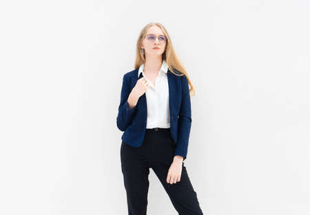 A portrait of young caucasian blonde business woman in glasses standing in front of a white wall and looking away. The right hand holds a jacket. She is dressed in black pants, blue jacket and a white short-sleeved shirt. Concept of successful young women. Lifestyle concept. Copy space. Space for text. Stock Photo