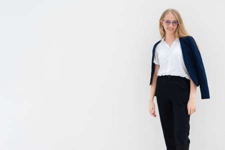 A portrait of young caucasian blonde business woman in glasses standing in front of a white wall, smiling and looking to the camera. Her hands are down. She is dressed in black pants, blue jacket and a white short-sleeved shirt. Concept of successful young women. Lifestyle concept. Copy space. Space for text. Stock Photo