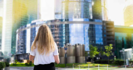Back view of a young caucasian blonde business woman walks through the business district. Successful business woman concept. Lifestyle concept. Copy space. Space for text.