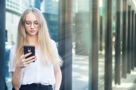 Portrait of a cheerful young caucasian blond business woman holding and looking at phone and thinking. Concept of successful young women in a corporation. Girl in a white shirt. Horizontal photo. Blurred background. Plants on the background.