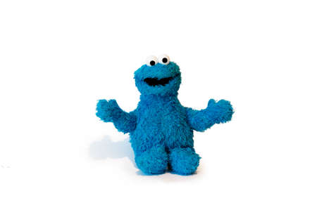 Soft blue cookie monster plushie toy isolated on white background with shadow reflection. The concept of gifts for the holidays. Sesame street character. Side wiew