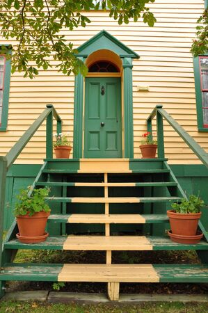 stairs leading to a green door on a old yellow house