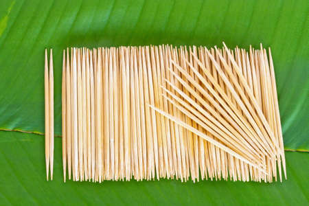 Many scattered toothpicks on banana leaf photo