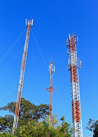 Three Communication Towers stand in the blue sky photo