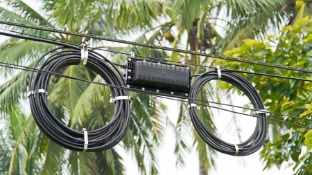 closure: Black optical fiber cable used in telecommunications hanging on post
