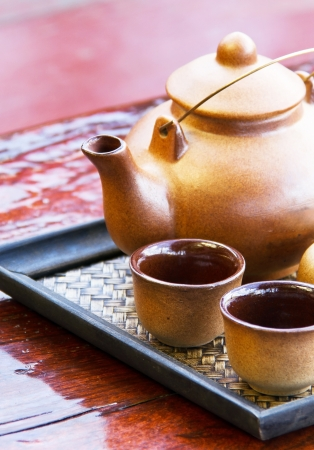 Cups of tea and teapot on wooden table photo