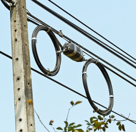 Black optical fiber cable used in telecommunications hanging on post