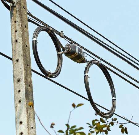 fibra �ptica: Cable de fibra ?ptica negro utilizado en telecomunicaciones colgando en el poste Foto de archivo