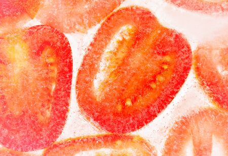 Macro view of cut shape tomato in ice background photo