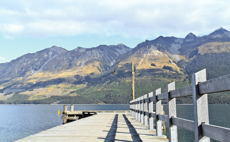 Empty dock in calm lake with mountains, South Island, New Zealand photo