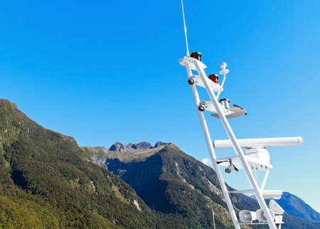 anemometer: Radar and anemometer of cruise ship over mountain and clear blue sky Stock Photo