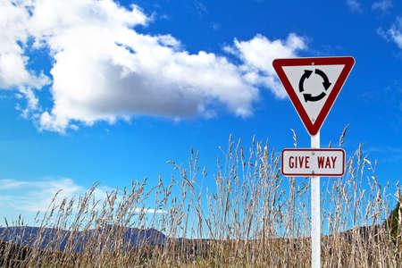 Traffic sign over dry grass and blue sky photo