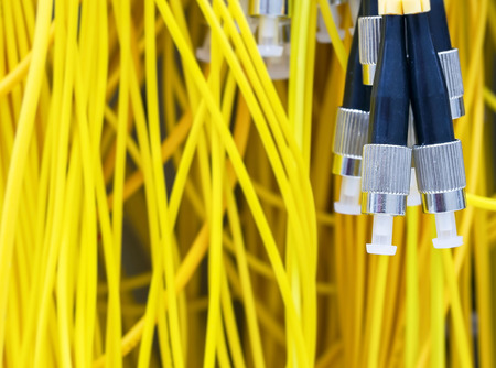 Yellow optical fiber with connector of FC type pig tail in server room photo