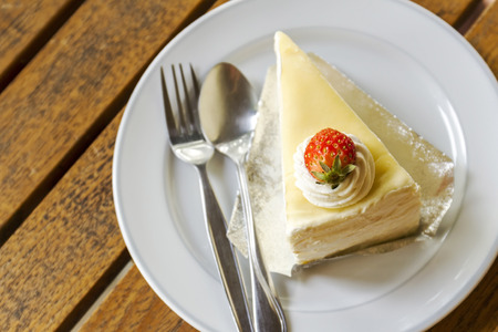Delicious of strawberry crepe cake on wooden table, top view photo
